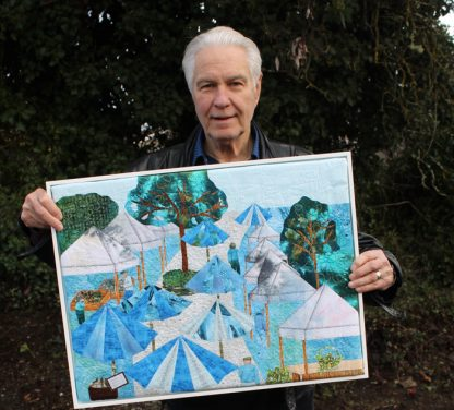 Salt Spring's electoral area director Wayne McIntyre holds the Salt Spring panel of the CRD 50th Anniversary Quilt. Fabric artist Karen Tottman created the market-themed art piece.