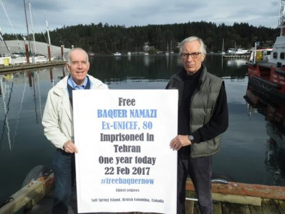 """Tony Kennedy, left, and Nigel Fisher hold a """"Free Baquer Namazi"""" sign marking the one-year date of his imprisonment in Tehran today (Feb. 22)."""