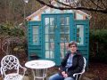 "Shelley Armstrong-Plaunt sits outside of her colourful ""she-shed,"" perfect for eating outdoors in summer months."