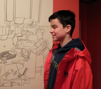 Artist Karen Andrews' son Sam with a drawing of him done by his mother, part of The Point gallery exhibit that opens Sunday, April 2.
