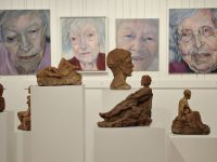 OJ Clarke fired clay sculptures are backed by Susan Benson portraits at Body of Work, a Salt Spring Arts Council exhibition featuring 20 artists at Mahon Hall.